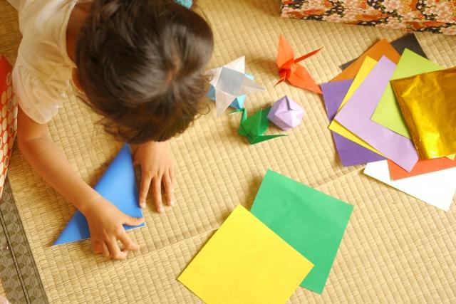 折り紙を一所懸命に折る子供
