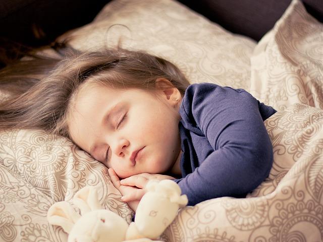 羽毛布団で気持ち良さげに眠る子供