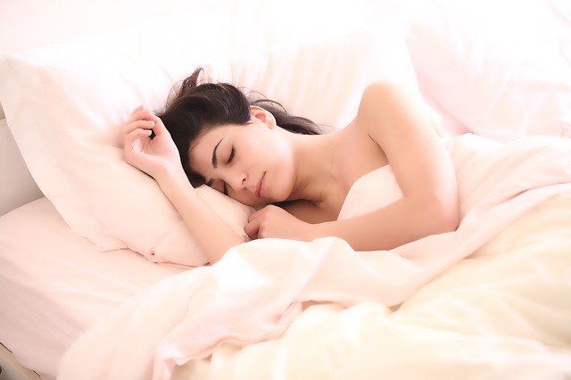 ベッドで羽毛布団にくるまり眠っている女性