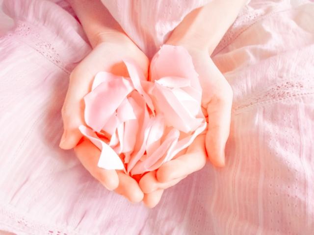 汗をかいていない両手にバラの花びらをもつ